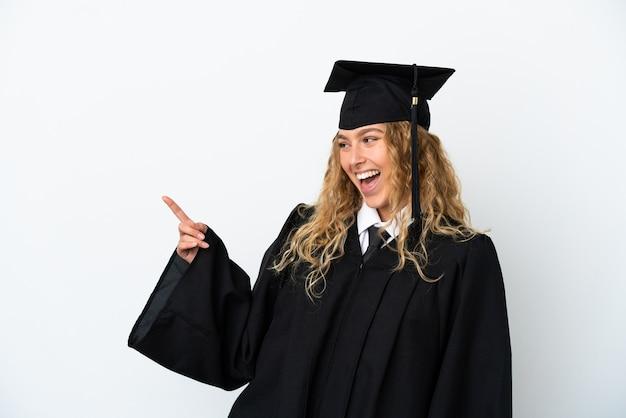 Graduado universitario joven aislado sobre fondo blanco apuntando con el dedo hacia un lado y presentando un producto