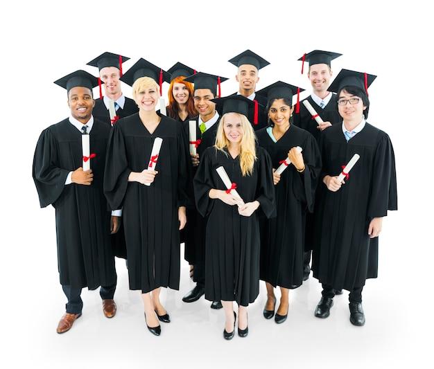 Los graduados de los estudiantes con su diploma con gran smilling.