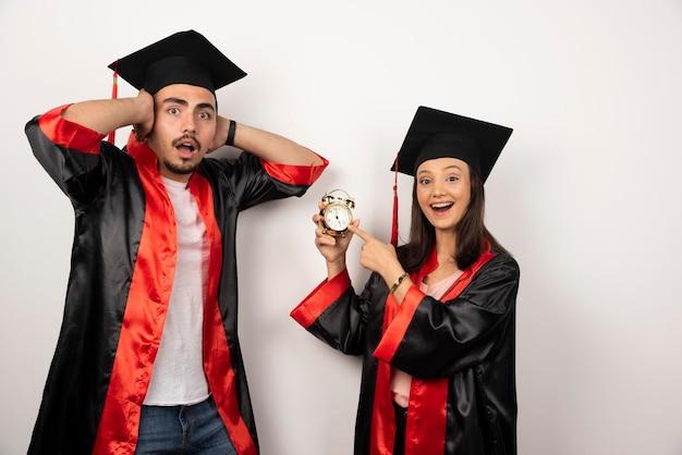 Graduados frescos en vestido mostrando tiempo en blanco.