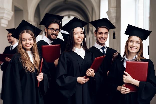 Los graduados se paran con diplomas en el lobby de la universidad.