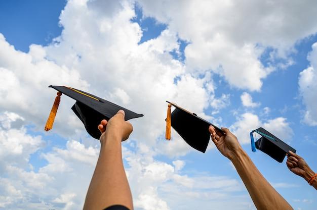 Los graduados tiran sombreros el día de la graduación en la universidad.