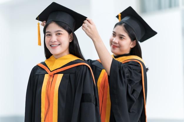 Graduados universitarios femeninos con sombreros negros, borlas amarillas, sonrientes y felices el día de la graduación