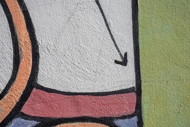 Graffiti inferior con flecha y fondo colorido