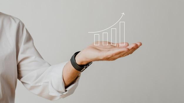 Gráfico de barras creciente digital con superposición de manos de empresario