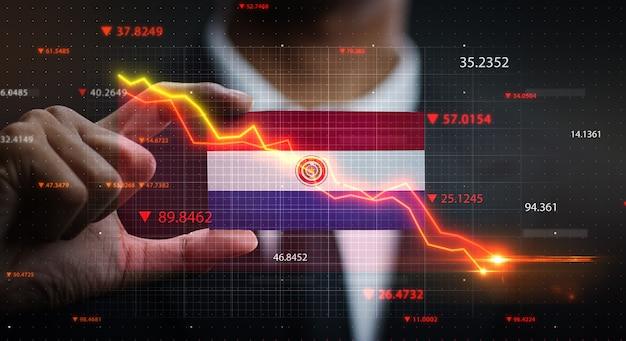 Gráfico cayendo frente a la bandera de paraguay. concepto de crisis
