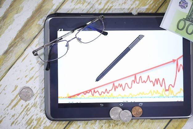 El gráfico de crecimiento de los ingresos. tableta electrónica con gráfico de tasas de crecimiento de ganancias. la moneda en el gráfico del teléfono inteligente.