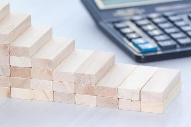 Gráfico decreciente de bloques de madera con calculadora. concepto financiero copia espacio