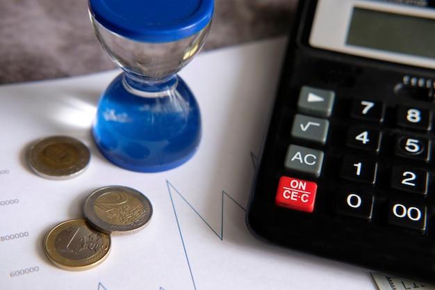 Gráficos financieros junto a una calculadora y algunas monedas de euro