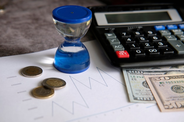 Gráficos financieros junto a una calculadora, monedas y billetes