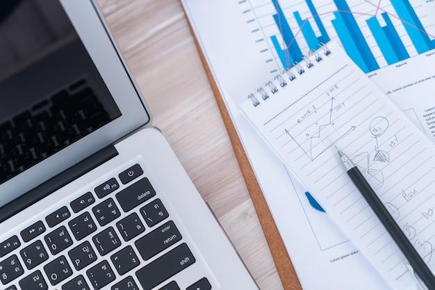 Gráficos financieros sobre la mesa con el ordenador portátil