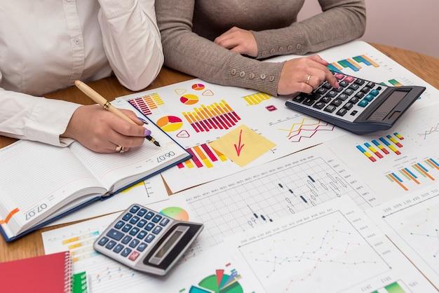 Gráficos de negocios con calculadora y manos femeninas