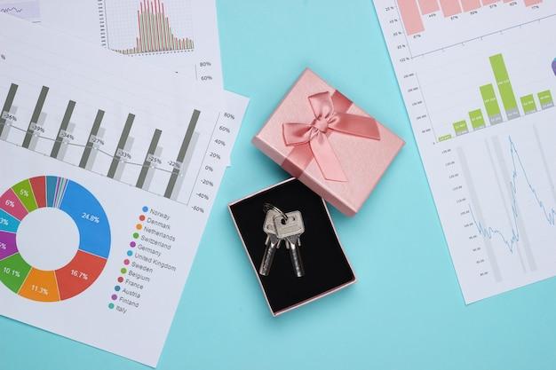 Gráficos y tablas, caja de regalo con llave. plan de negocios, analítica financiera, estadísticas. vista superior sobre fondo azul