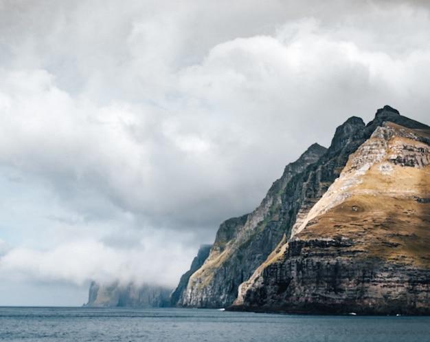 Gran acantilado rodeado por el agua bajo las nubes.