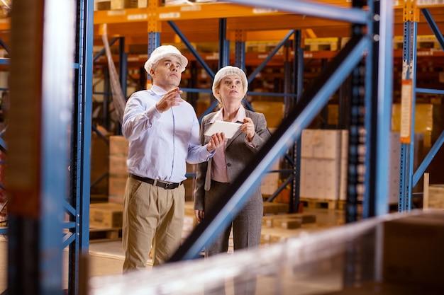 Gran almacén. gente amable inteligente de pie juntos y mirando hacia arriba mientras trabaja en el gran almacén