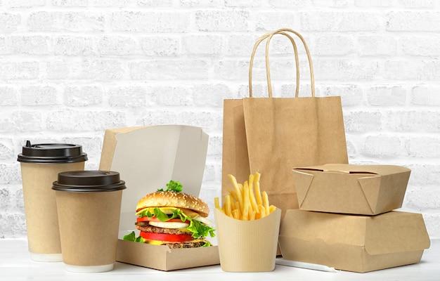 Gran almuerzo de comida rápida conjunto de sabrosa hamburguesa, papas fritas, tazas de café de papel, bolsa de papel marrón y caja en la mesa aislada sobre fondo blanco