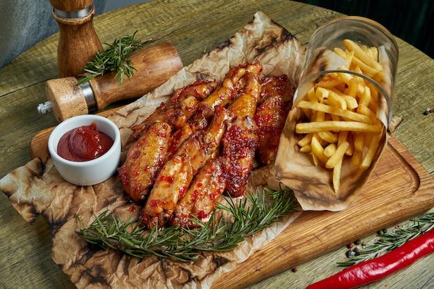 Gran aperitivo de cerveza - alitas de búfalo picantes al horno. alitas de barbacoa con guarnición de papas fritas en una bandeja de madera. vista superior, comida plana. comida de pub