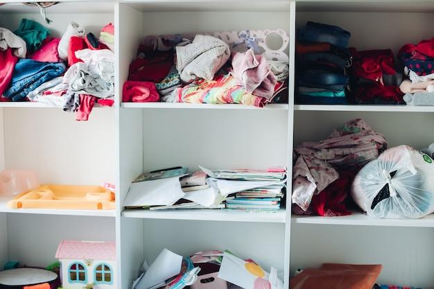 Un gran armario blanco con estantes cuadrados y cosas que no están dobladas.