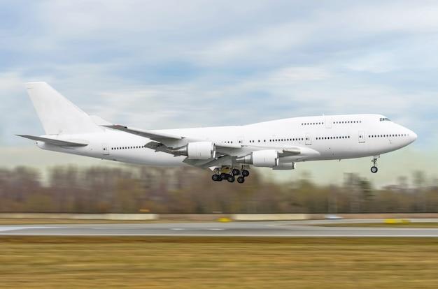 El gran avión de pasajeros blanco está aterrizando en la pista del aeropuerto.