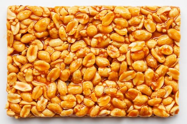 Un gran azulejo de barra de maní tostado en una dulce melaza. kozinaki útiles y sabrosos dulces de oriente