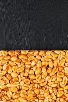 Un gran azulejo dorado de maní, una barra de melaza dulce. kozinaki útiles y sabrosos dulces de oriente