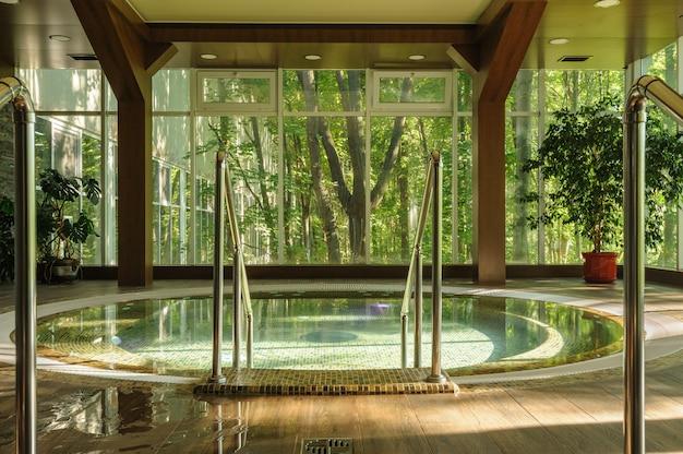 Gran bañera de hidromasaje redonda en el centro de spa, temprano por la mañana
