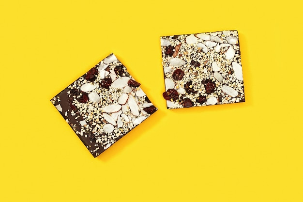 Gran barra de chocolate mordido con nueces y arándanos secos se divide en dos partes sobre fondo amarillo
