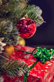 Una gran bola roja y una caja con un regalo debajo del árbol de navidad