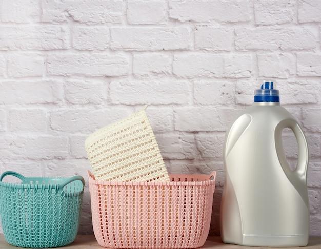 Gran botella de plástico con detergente líquido y una pila de cestas en la pared de ladrillo blanco.