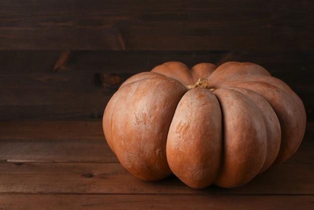 Gran calabaza madura sobre fondo de madera oscura. fea comida natural. calabaza en estado natural. cosas de halloween cosecha de otoño.