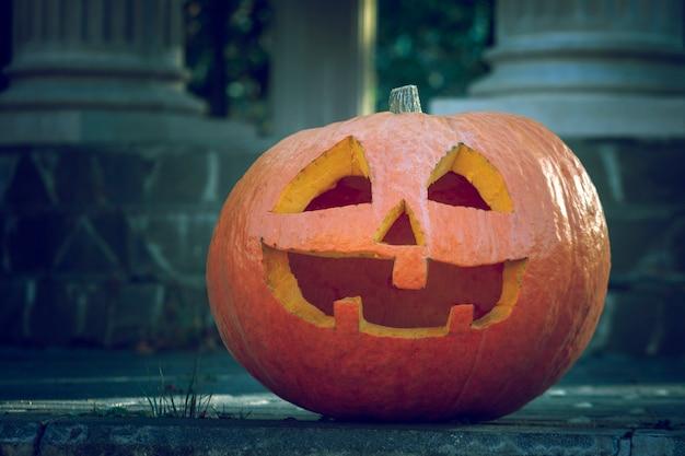 Una gran calabaza naranja con una cara tallada en el crepúsculo.