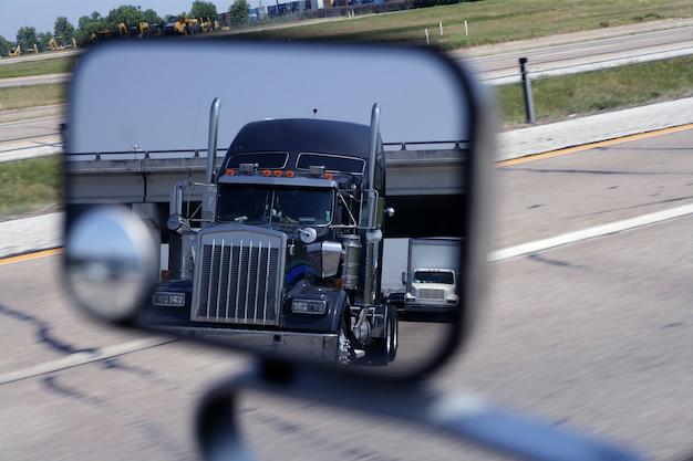 Un gran camión azul en el espejo del vehículo.