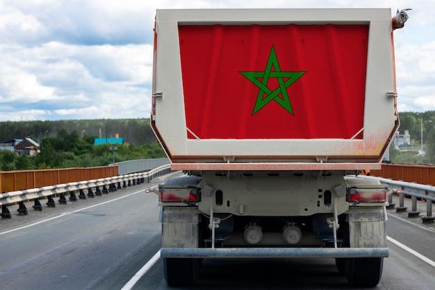 Gran camión con la bandera nacional de marruecos moviéndose en la carretera