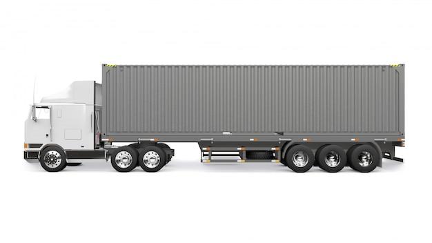 Un gran camión retro blanco con una parte para dormir y una extensión aerodinámica lleva un remolque con un contenedor marítimo.