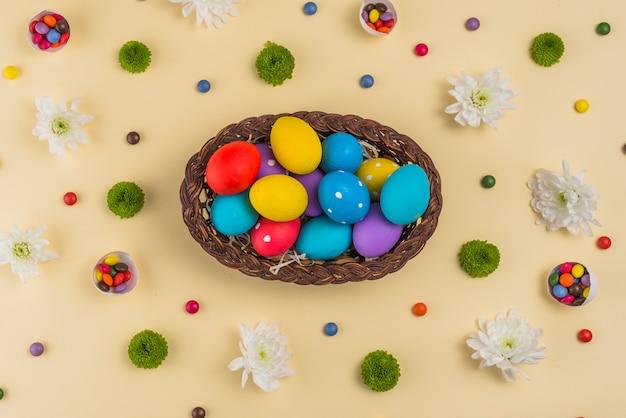 Gran canasta con coloridos huevos de pascua en mesa beige.