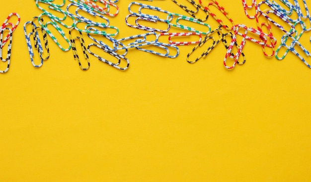 Gran cantidad de clips de papel de colores sobre fondo amarillo. concepto de oficina minimalista.