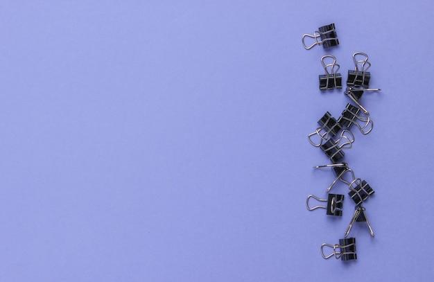 Gran cantidad de clips sobre un fondo morado. concepto de oficina minimalista