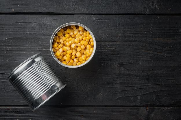 Gran cantidad de piezas de maíz amarillo enlatado en lata de metal, sobre fondo de mesa de madera negra, vista superior plana con espacio para copiar texto