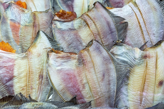 Gran cantidad de solla marina de pescado seco salado. fondo de peces planos de grupo con caviar. stock de pescado de la cocina asiática como aperitivo. vista plana en primer plano de mariscos del pacífico preparados y listos para comer.