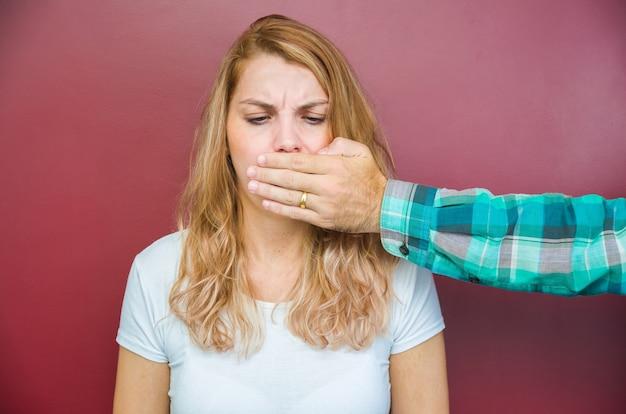 Gran concepto de censura masculina, mujer con la boca cubierta por la mano del hombre.