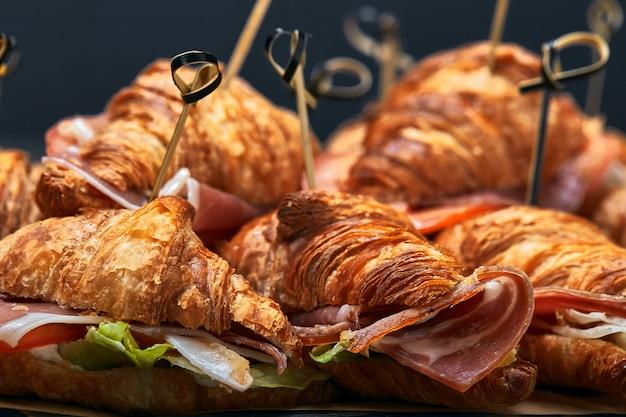 Un gran conjunto de muchos croissants con diferentes rellenos dispuestos sobre una mesa en una pared gris.