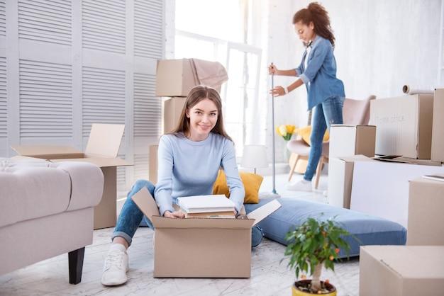 Gran cooperación. chica joven alegre sacando un montón de libros de la caja mientras su compañero de piso limpia el suelo con un trapeador
