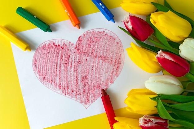 Gran corazón rojo dibujado en crayones de papel, lápices y ramo de flores coloridos tulipanes en amarillo