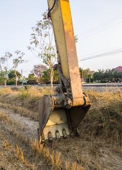 El gran cucharón con la garra afilada de la excavadora está tendido en el suelo en el sitio de construcción después de las horas de trabajo, vista frontal para el fondo.