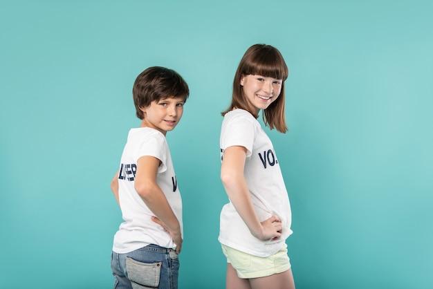 Gran día. alertar a los jóvenes voluntarios que visten camisetas similares y que estén de pie con las manos en la cintura.