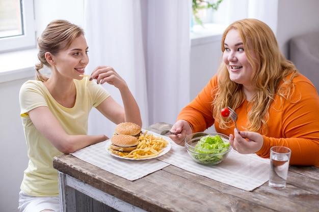 Gran día. mujer delgada alegre comiendo comida rápida y hablando con su amigo gordo comiendo una ensalada