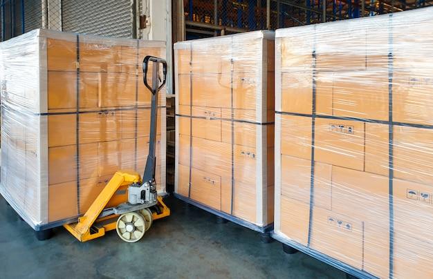 Gran envío de mercancías paletizadas con transpaleta manual en el almacén.