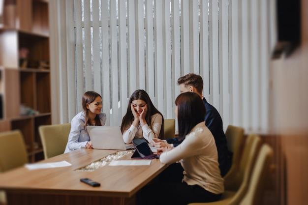Un gran equipo de personas está trabajando en una mesa para computadoras portátiles, tabletas y papeles.