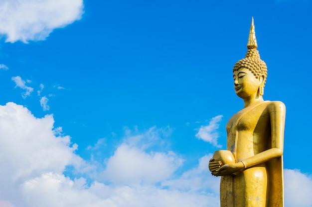 Gran estatua dorada de buda con fondo de cielo azul