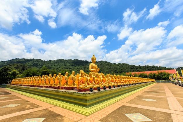 Gran estatua dorada de buda y muchas pequeñas estatuas doradas de buda sentadas en fila en el buddha memorial park