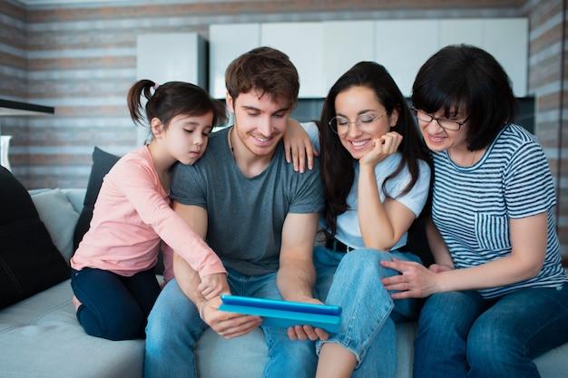 Gran familia en casa. todos juntos comunican conferencias en línea en la tableta.